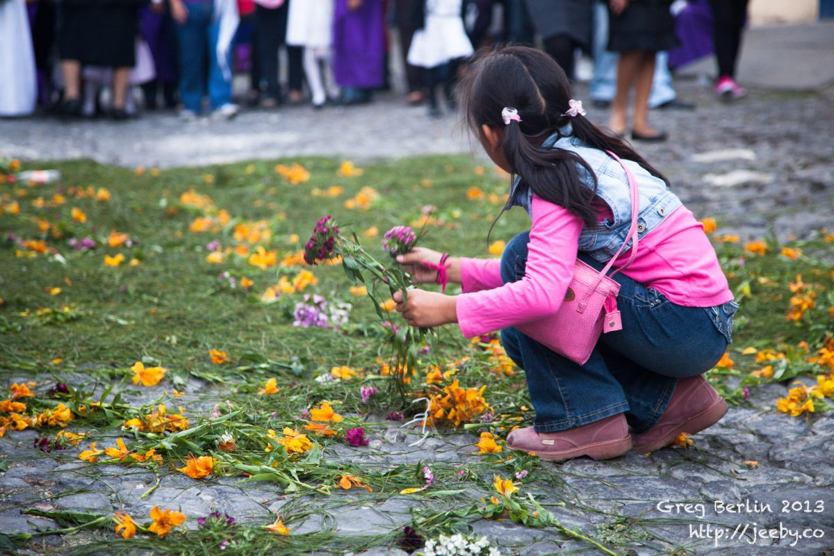 Girl collects flowers after Semana Santa parade in Antigua, Guatemala